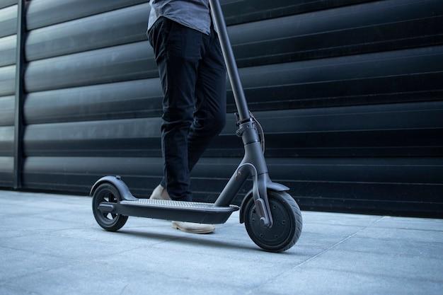 Persoon die door zijn elektrische scooter loopt