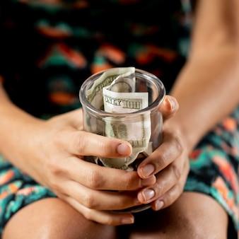 Persoon die duidelijke pot met bankbiljetten houdt