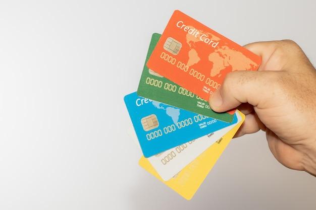 Persoon die een aantal kleurrijke creditcards over een wit houdt