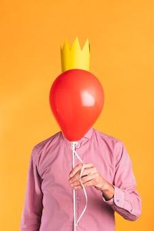 Persoon die een ballon op oranje achtergrond houdt