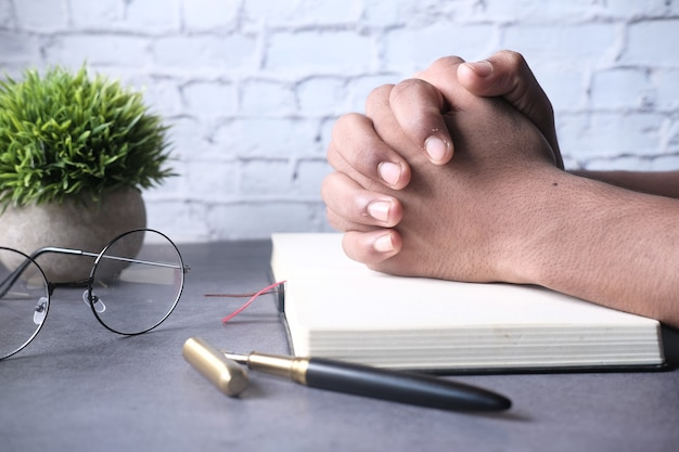 Persoon die een bijbel in zijn handen houdt en bidt.