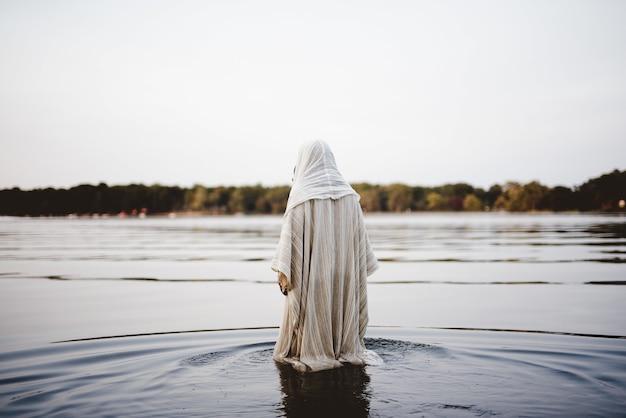Persoon die een bijbelse mantel draagt die in het water loopt