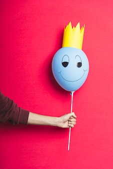 Persoon die een blauwe ballon op rode achtergrond met exemplaarruimte houdt