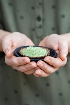 Persoon die een bord met groen poeder vasthoudt dat wordt gebruikt voor rauw veganistisch voedsel