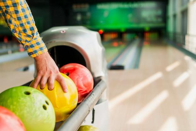 Persoon die een bowlingbal neemt