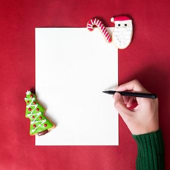 Persoon die een brief met smakelijke kerstmis eigengemaakte koekjes schrijft