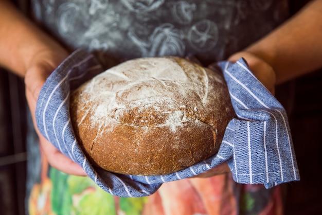 Persoon die een broodje vooraanzicht houdt