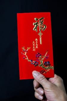Persoon die een chinese traditionele rode envelop houdt voor de viering van chinees nieuwjaar