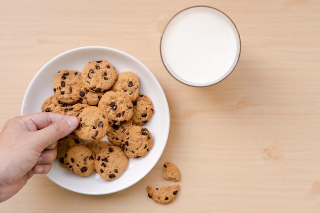 Persoon die een chocoladeschilferkoekje uit de schotel en melk op de houten lijst plukt