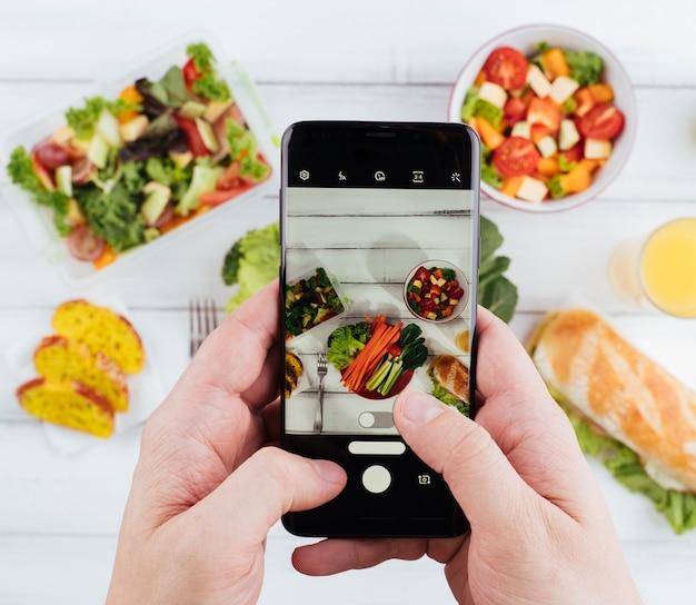 Persoon die een foto van heerlijk gezond voedsel neemt