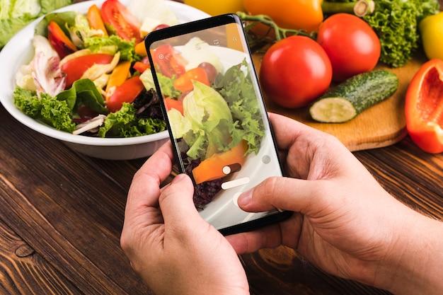 Persoon die een foto van salade neemt