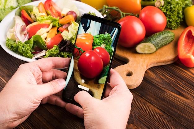 Persoon die een foto van tomaten neemt
