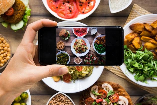 Persoon die een foto van verschillende veganistische gerechten neemt