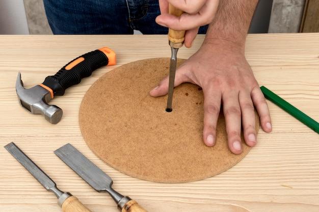 Persoon die een gat in een stuk hout maakt