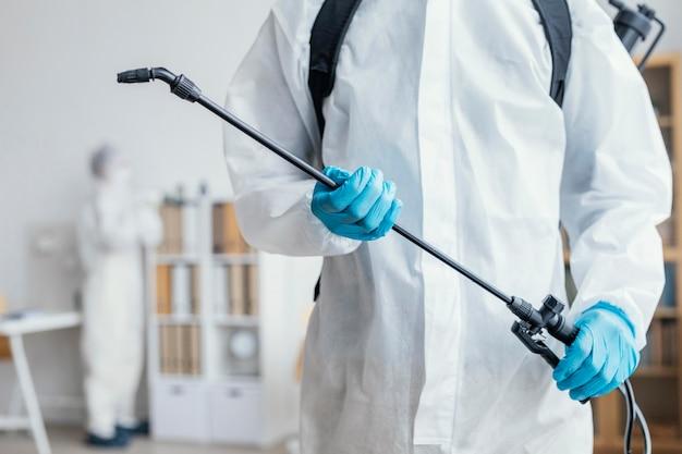 Persoon die een gevaarlijk gebied desinfecteert terwijl hij een beschermend pak draagt
