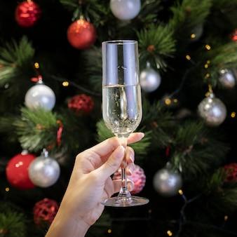 Persoon die een glas met kerstmisachtergrond houdt