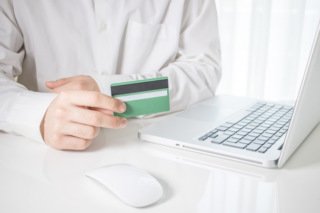 Persoon die een groene creditcard met laptop en een computermuis op een witte lijst houdt