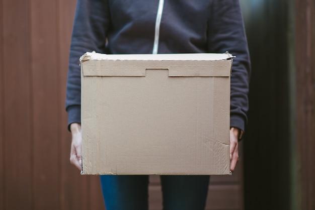 Persoon die een kartonnen doos