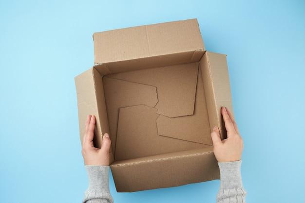 Persoon die een lege open doos bruin karton houdt