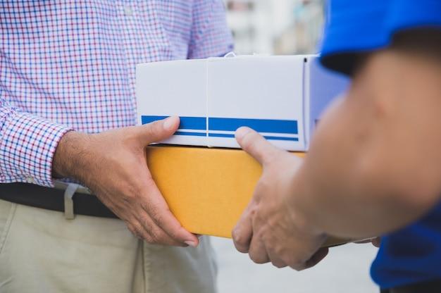 Persoon die een levering van dozen van bezorger accepteert