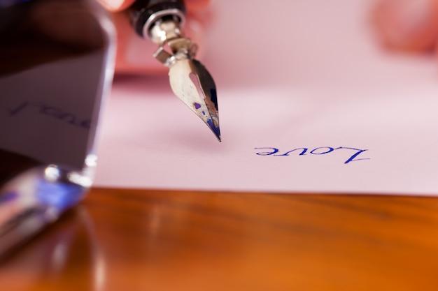 Persoon die een liefdesbrief met pen en inkt schrijft