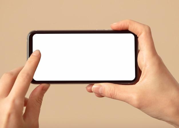 Persoon die een mobiele telefoon met een wit scherm houdt