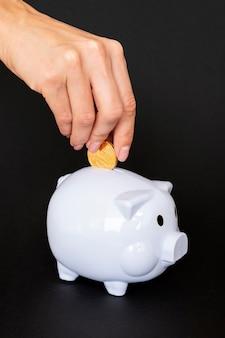 Persoon die een munt in een spaarvarken plaatst