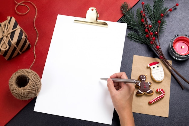 Persoon die een nota met smakelijke kerstmis eigengemaakte koekjes schrijft
