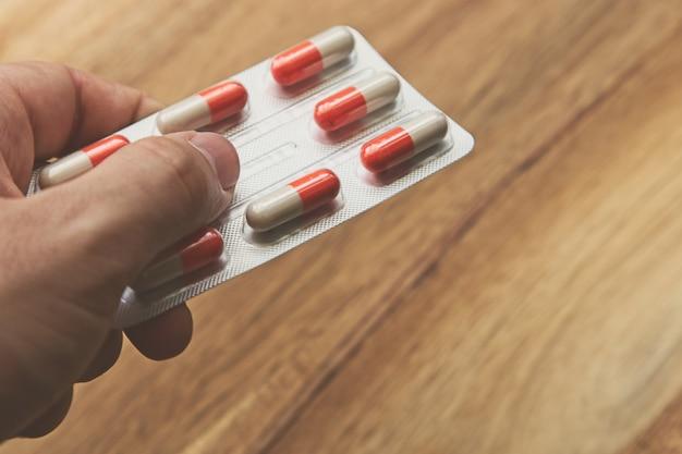Persoon die een pakje capsules op een houten oppervlak houdt