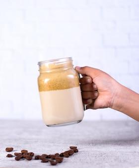 Persoon die een pot karamel smoothie over koffiebonen achter een wit houdt