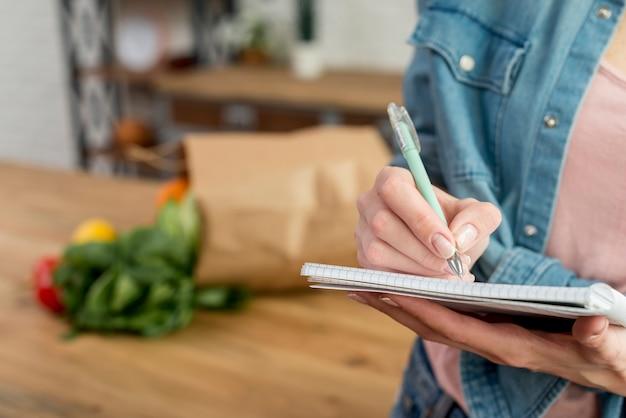 Persoon die een recept in het notitieboekje schrijft