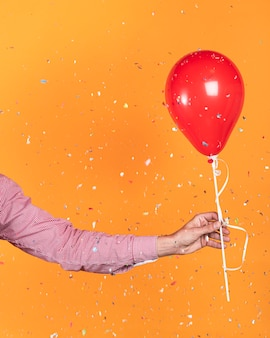 Persoon die een rode ballon en confetti houdt