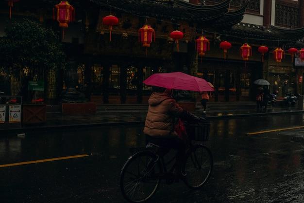 Persoon die een roze paraplu houdt berijdend een fiets in een natte straat dichtbij een chinees traditioneel gebouw