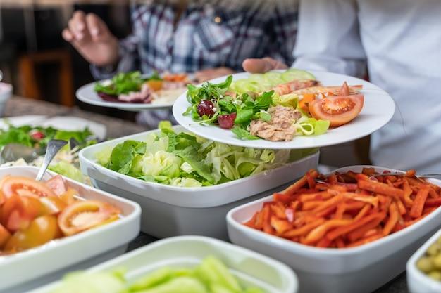 Persoon die een saladeplaat voor een voedselteller houdt bij een zelfbedieningsrestaurant