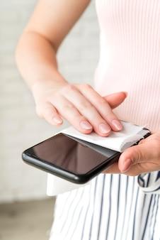 Persoon die een smartphone desinfecteert