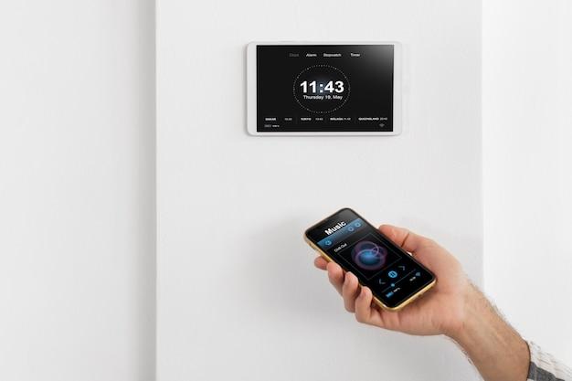 Persoon die een smartphone gebruikt in een geautomatiseerd huis