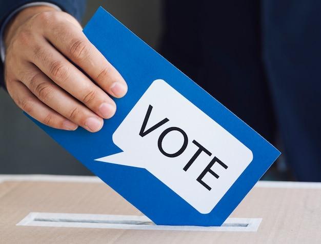 Persoon die een stemming in een verkiezingsdoos zet