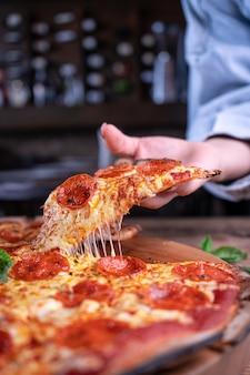 Persoon die een stuk heerlijke cheesy pepperoni-pizza krijgt