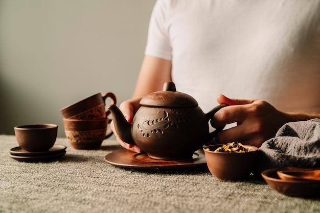 Persoon die een theepot houdt die met heerlijke drank wordt gevuld