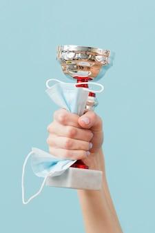 Persoon die een trofee en een medisch masker houdt