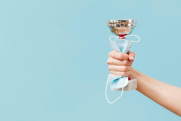 Persoon die een trofee en een medisch masker met exemplaarruimte houdt