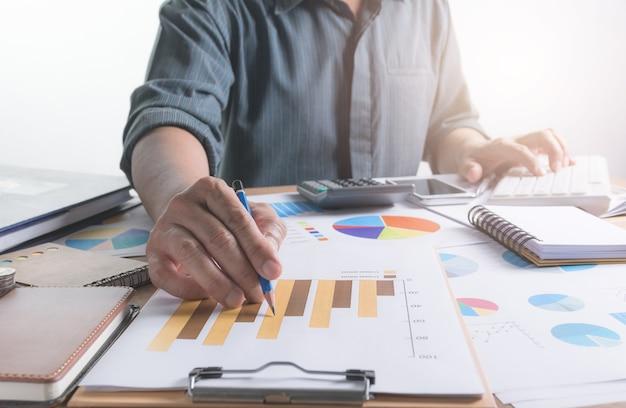 Persoon die en een computer voor financieel en boekhoudingsconcept werkt gebruikt