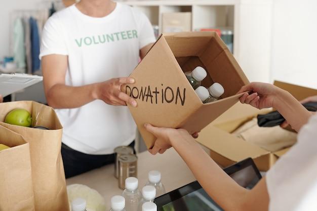 Persoon die flessenwater doneert aan een goed doel komt binnen en geeft een doos aan vrijwilligers