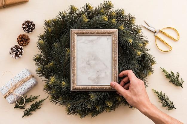 Persoon die frame op de kroon van kerstmis zet