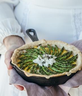 Persoon die gekookt voedsel in het koken van pan houdt