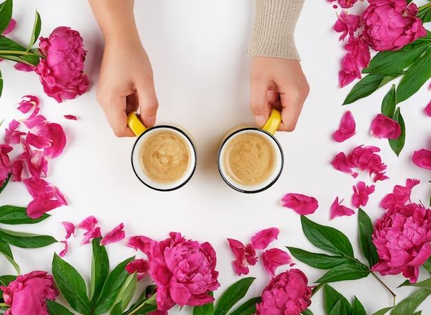Persoon die gele koppen met een hete koffiedrank op een witte oppervlakte in het midden van bloeiende pioenenknoppen houdt