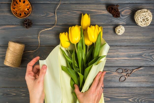 Persoon die gele tulpen verpakken in pakpapier