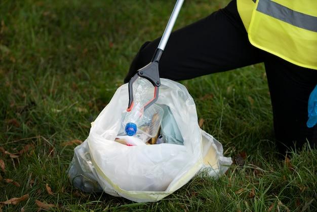 Persoon die gemeenschapsdienst doet door afval te verzamelen