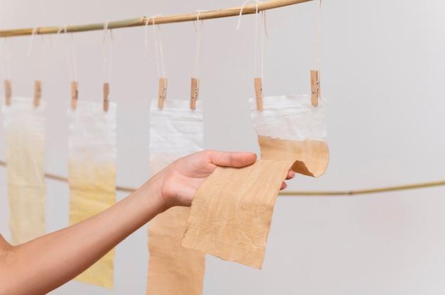 Persoon die gepigmenteerde doeken plaatst om te drogen