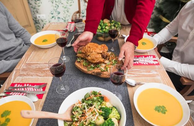 Persoon die geroosterde kip op feestelijke lijst zet